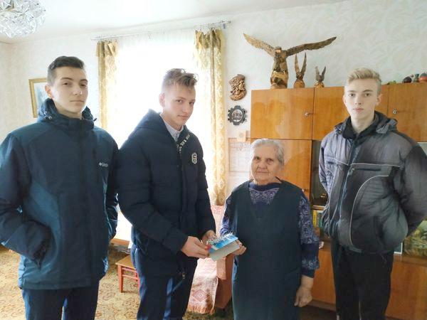 Мисеич Егор вручает поздравительную открытку Маханько М.Ф.