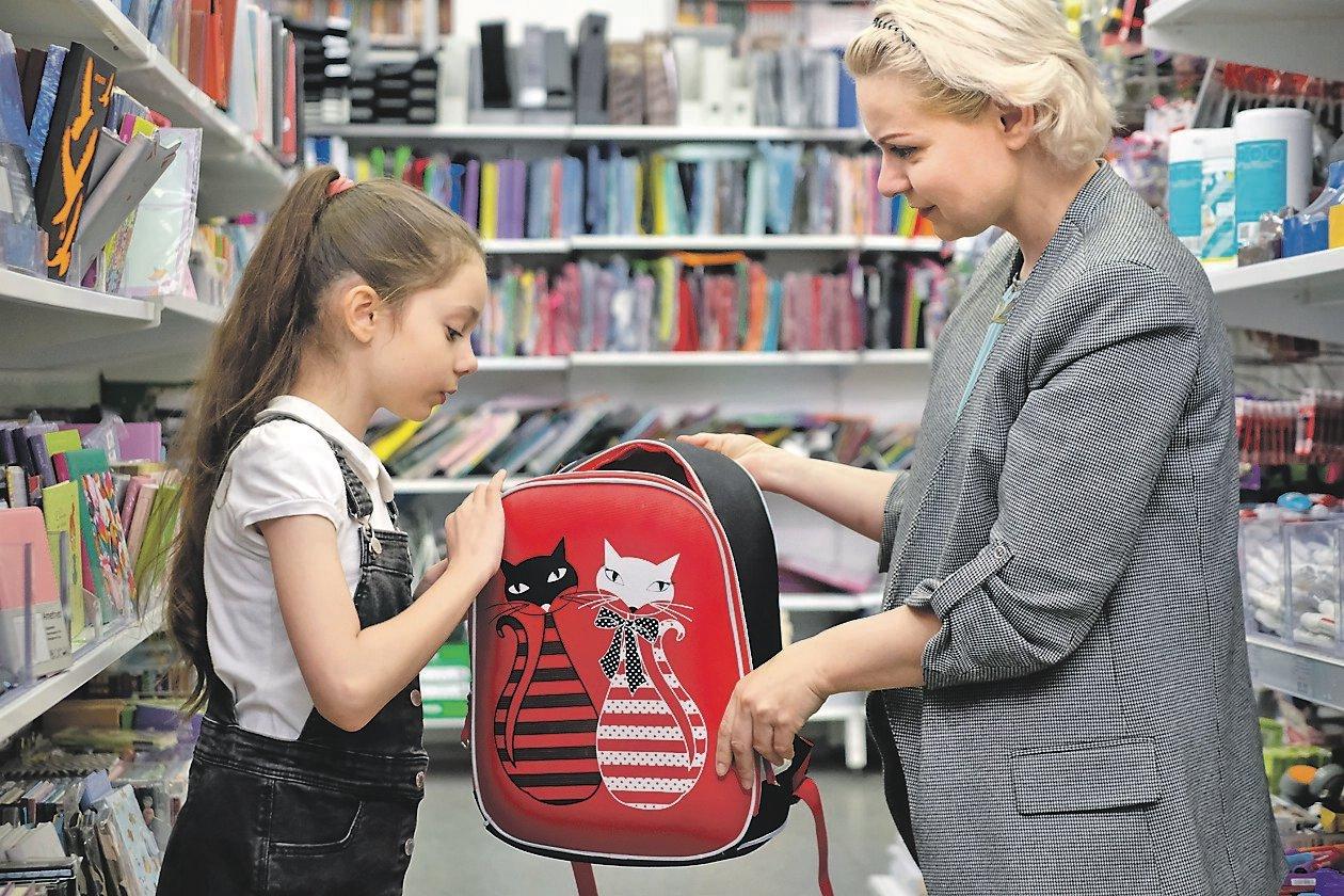 Санкт-Петербург. Женщина с девочкой выбирают рюкзак в отделе школьных принадлежностей в магазине канцтоваров перед началом учебного года.